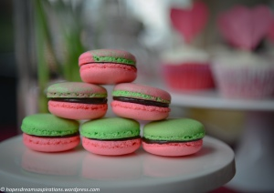 pink and green watermelon macarons on white cake stand