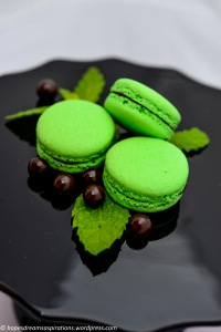 green macaron on black cake stand with mint and chocolate pearls