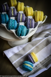 teal, purple and yellow macarons on white porcelain egg case and white cake stand